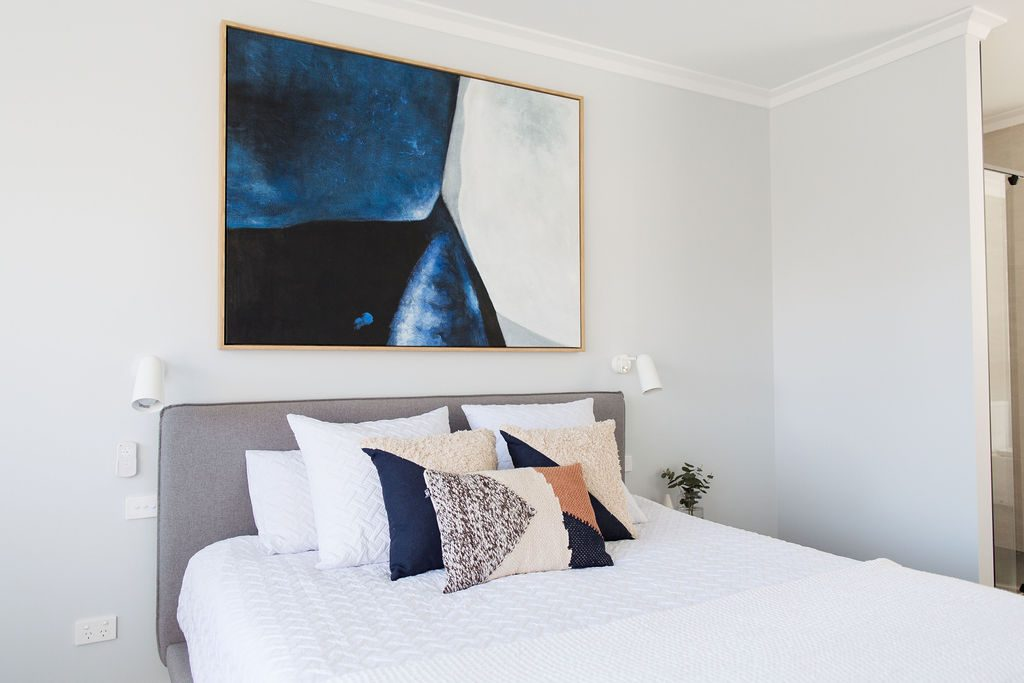 Modern master bedroom with feature artwork above bed