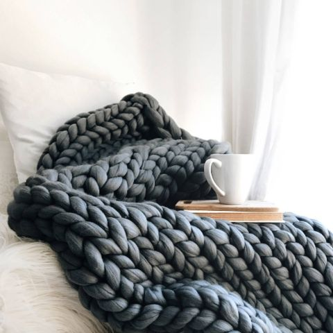 Chunky woollen grey blanket with cup of coffee