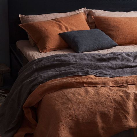 Bed with dusty pink, terracotta and blue bed linen