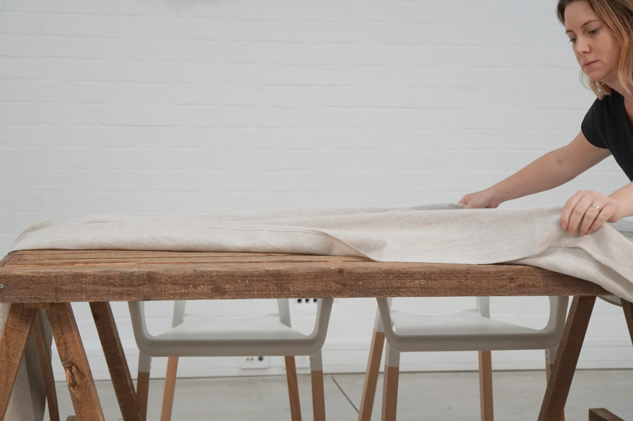 stylist laying out linen table cloth on table