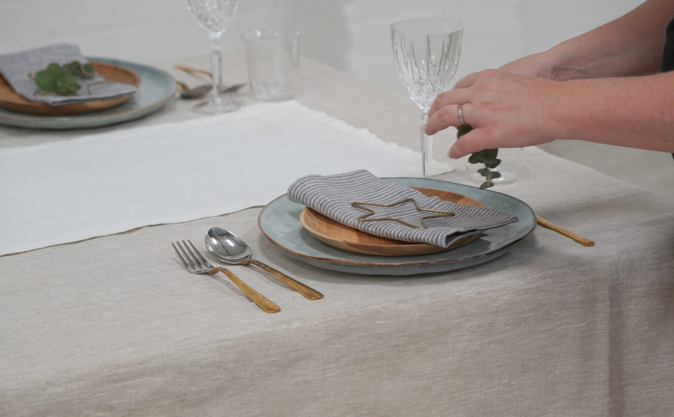 stylist setting up plates and napkins for table setting